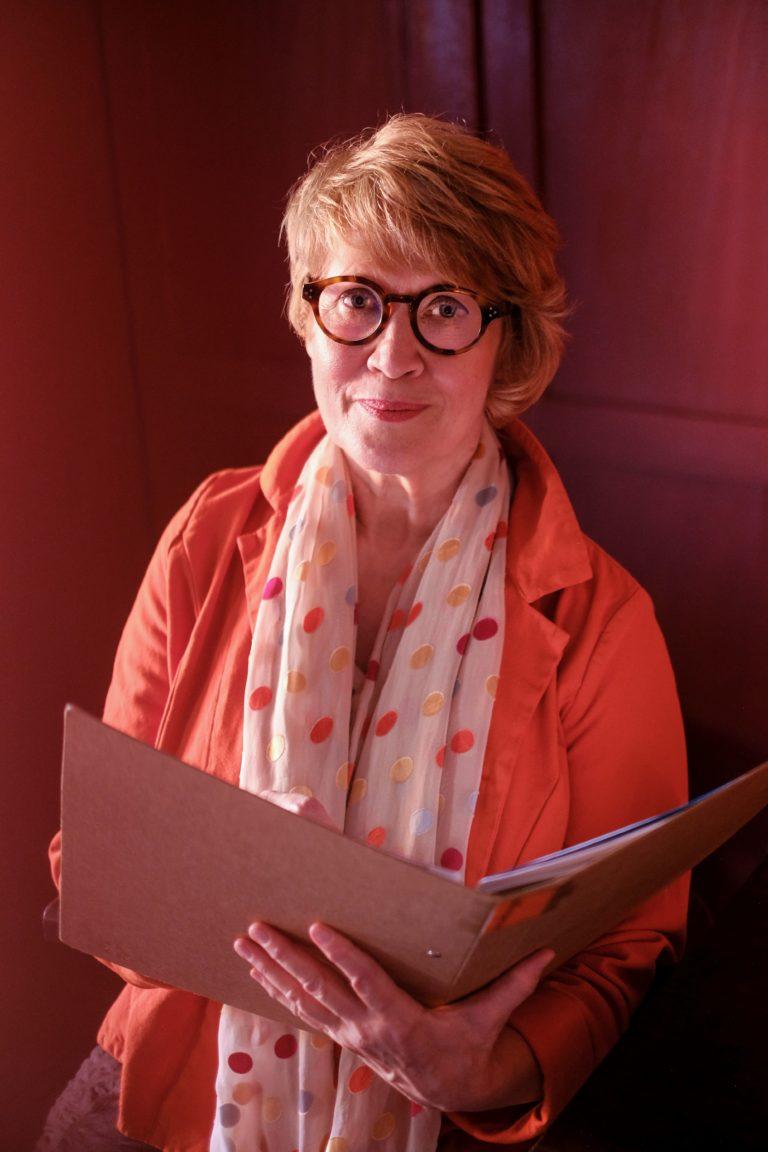 Susanne in orange mit Ordner