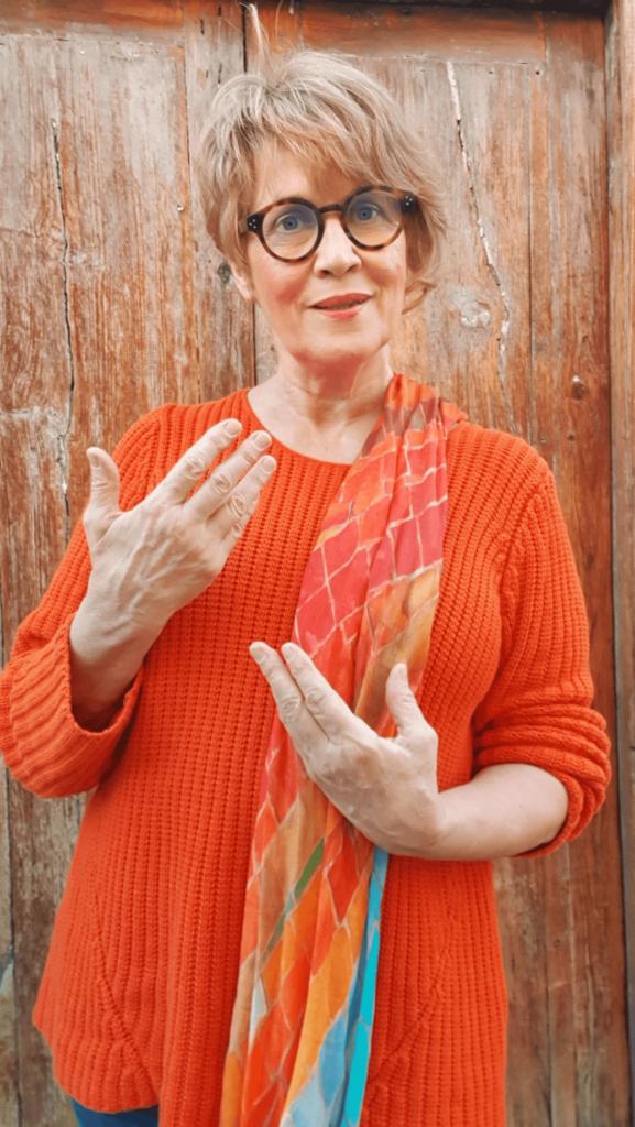 Susanne mit orangen Pullover beim Austausch mit anderen